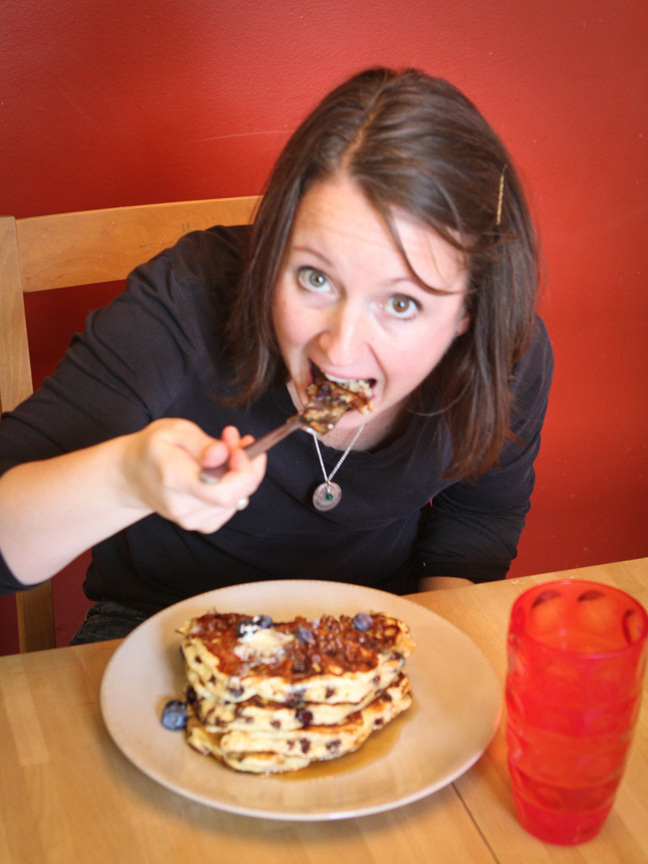 a hungry lady taking a bite out of a huge stack of pancakes