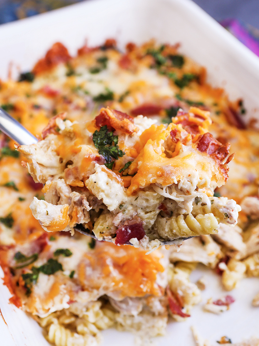 spoonful of chicken bacon ranch casserole being scooped out of pan