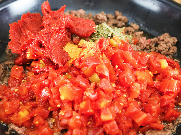 Skillet with cooked ground beef and tomato paste, rotel tomatoes and seasonings