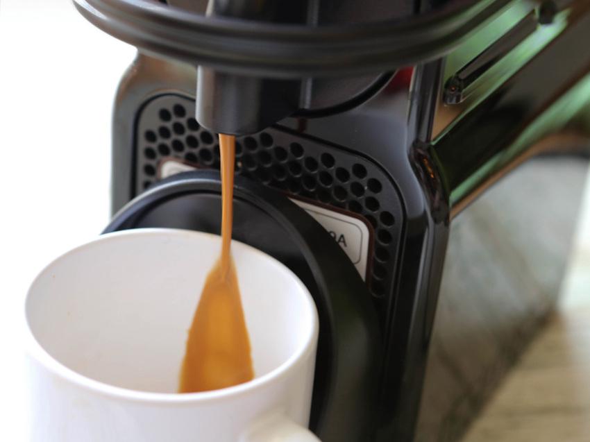 Coffee pouring out of Nespresso into a mug