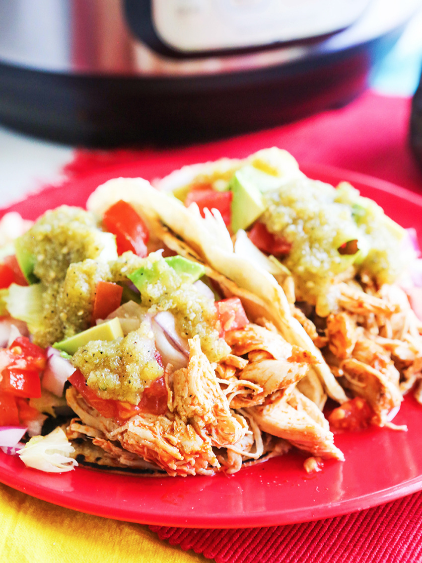 Two chicken tacos on a plate with toppings