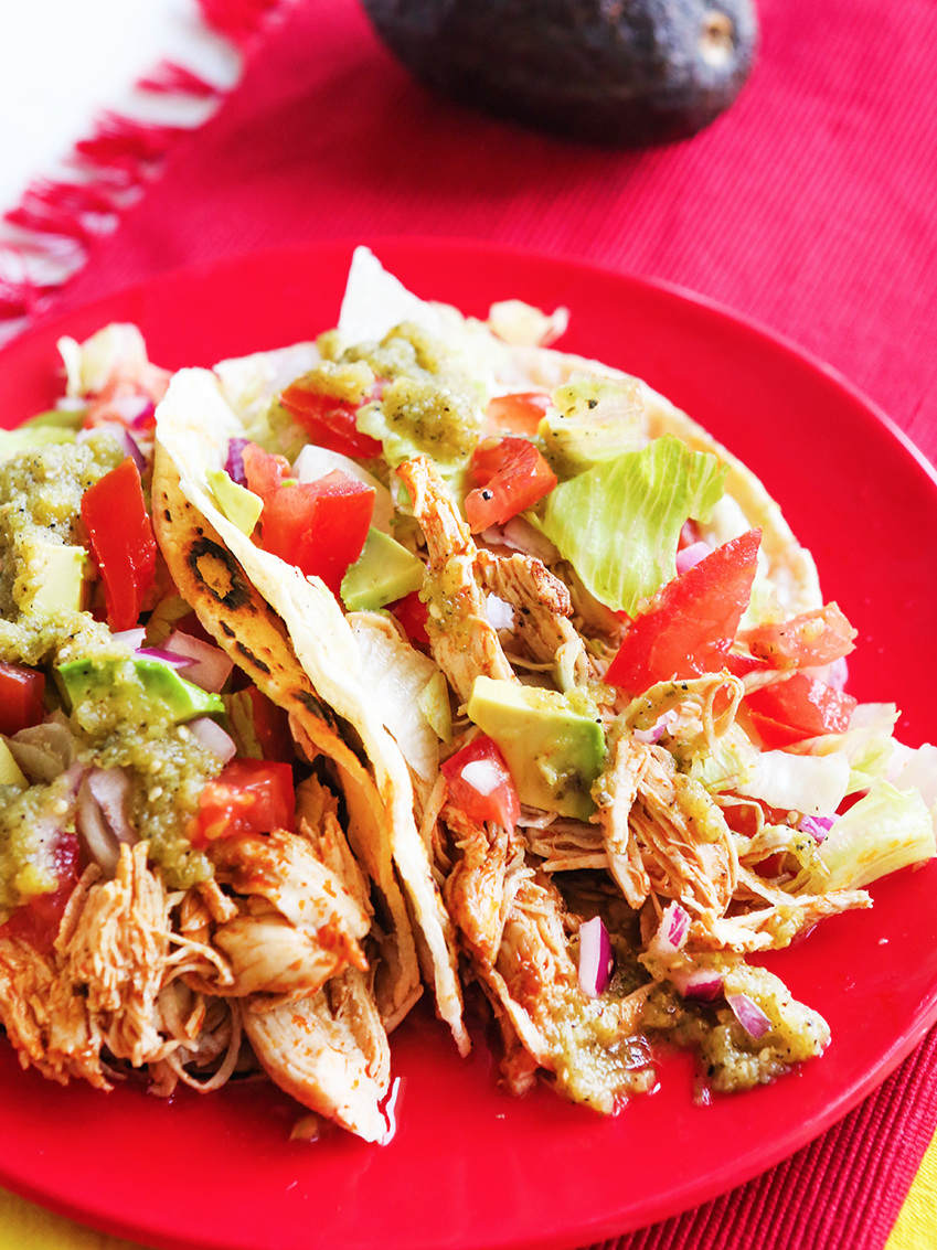 Top view of chicken tacos with tomatoes and lettuce