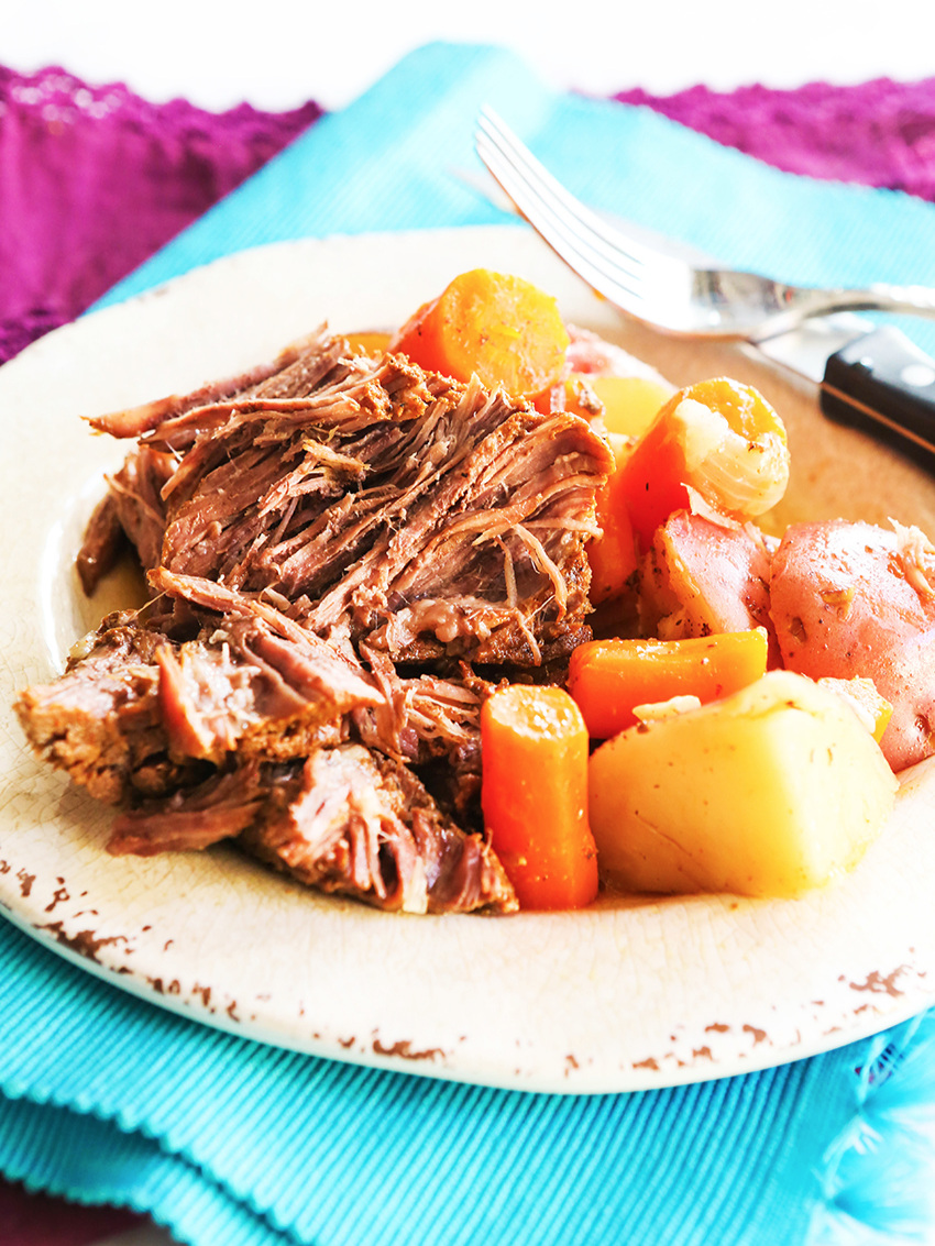 plate full of pot roast, cooked potatoes and carrots with a fork and knife on the plate.