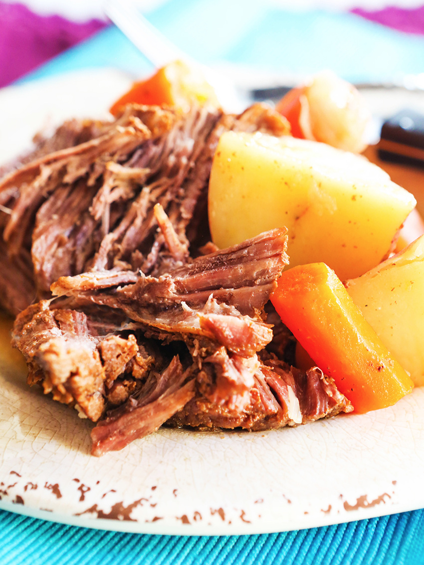 close up of a plate of pot roast, potatoes and carrots