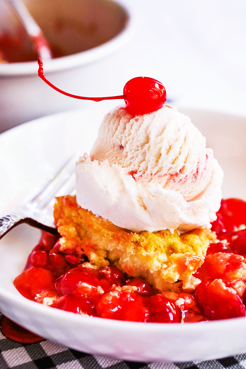 Serving of cherry dump cake with a scoop of ice cream in bowl