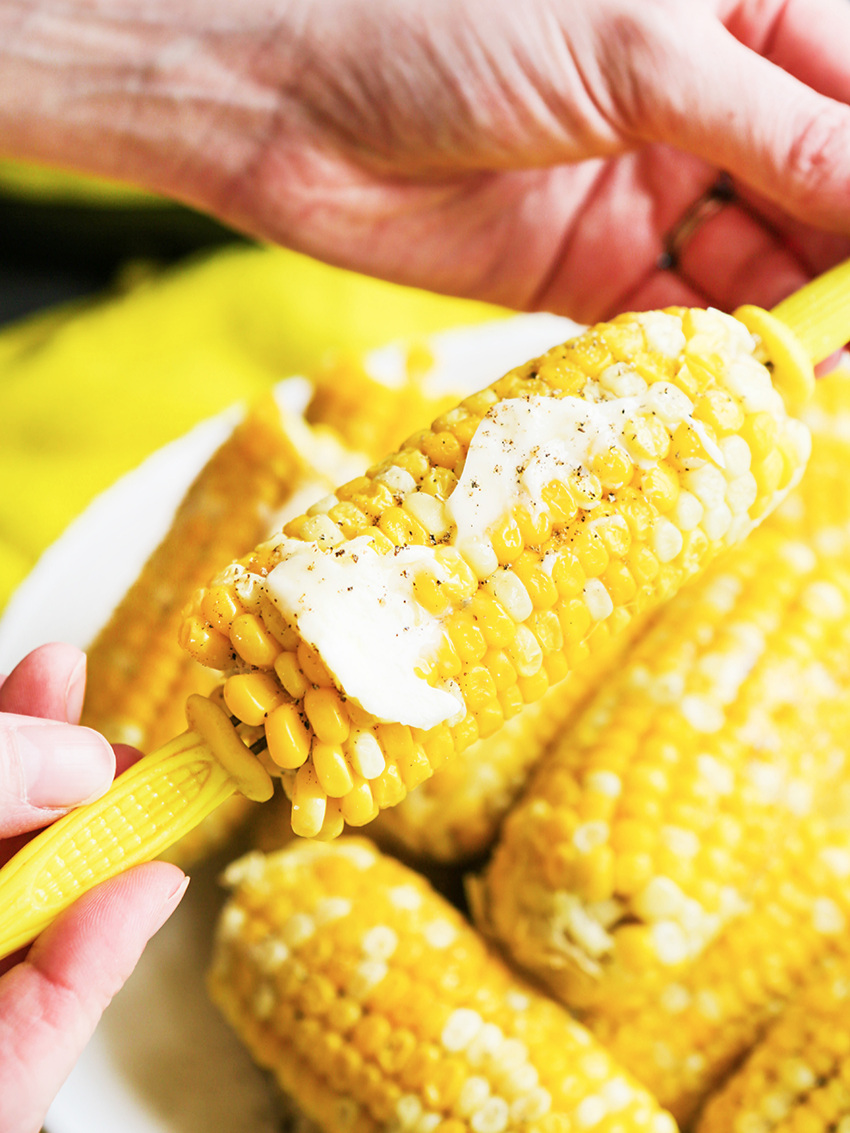 Hands holding a corn cob dripping with butter