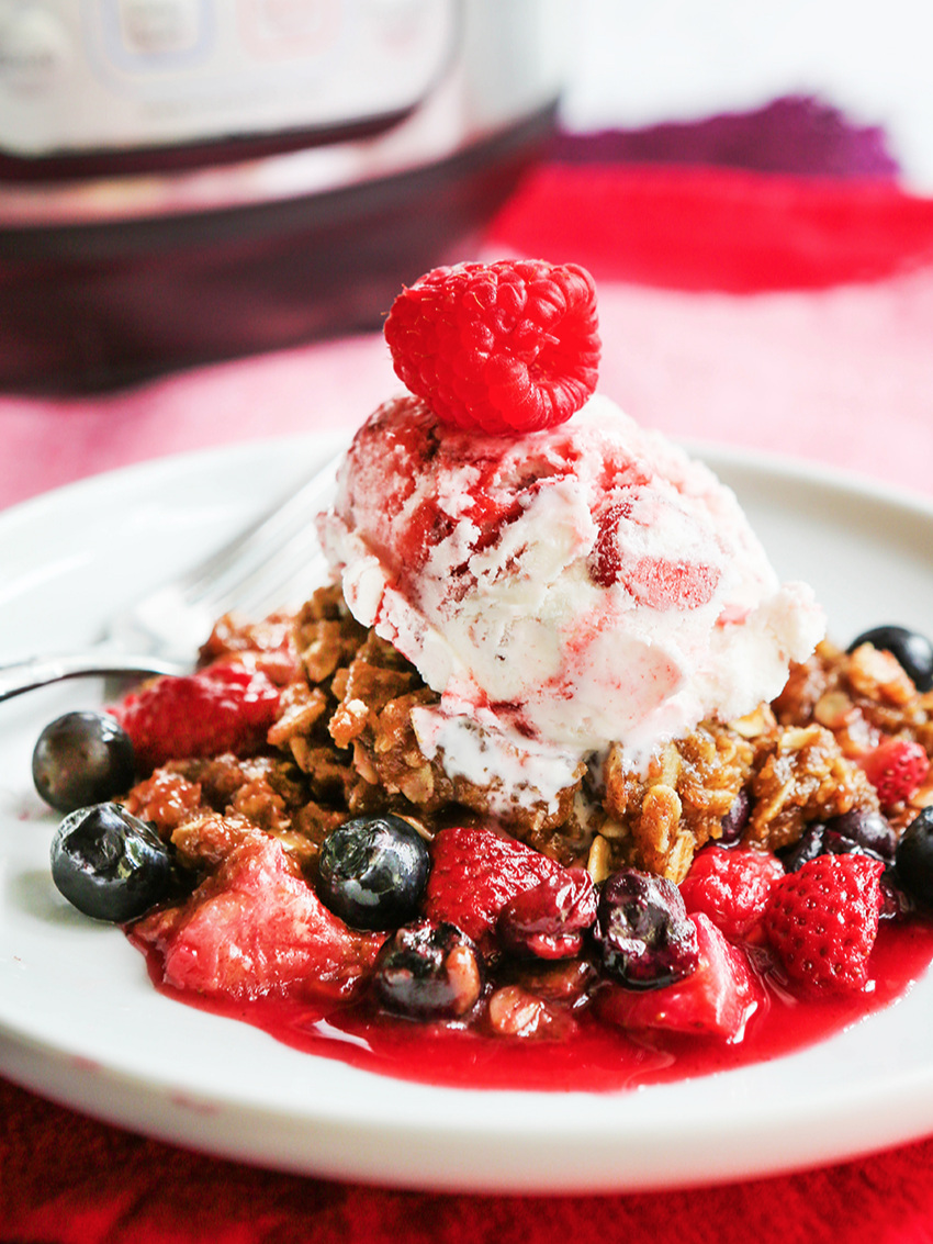serving of berry crisp with a scoop of ice cream and raspberry on top