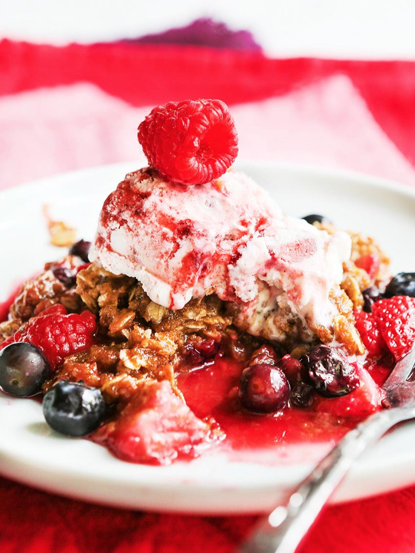 berry crisp with ice cream and berries surrounding it