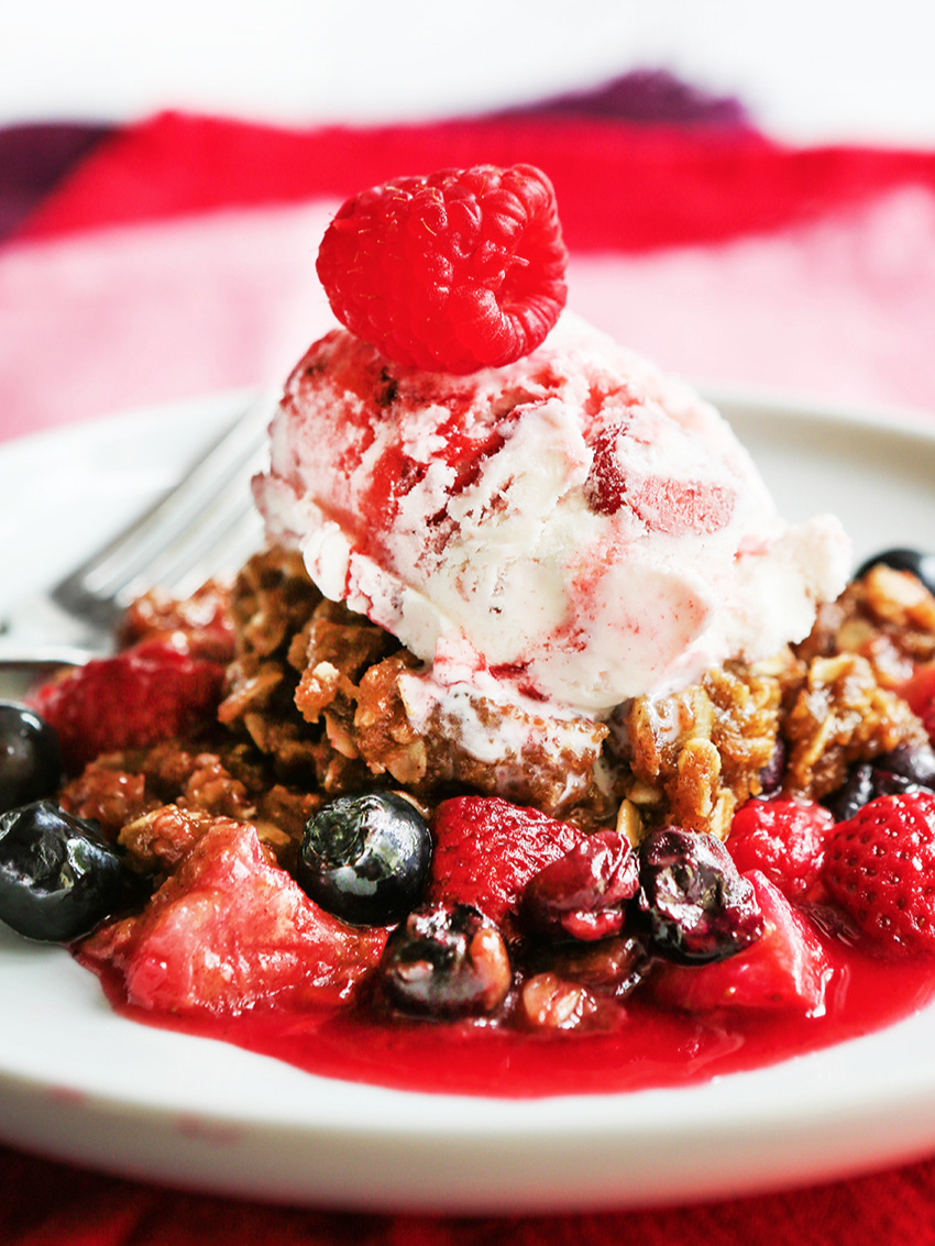 close up of berry crumble with ice cream on top