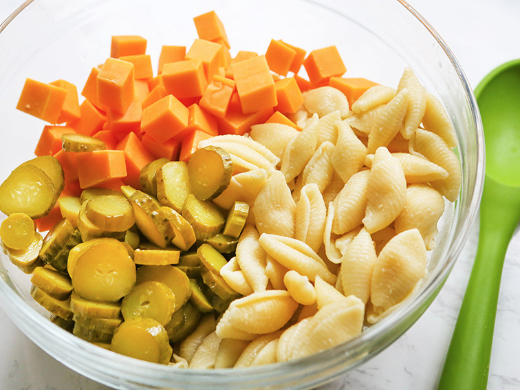 cheese, dill pickles and cooked pasta in a bowl with a green spoon on the table
