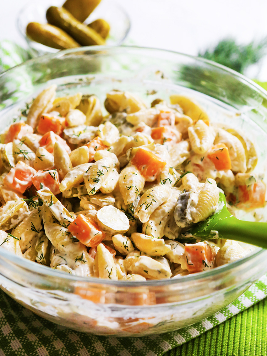 Green serving spoon in a bowl of dill pickle pasta salad