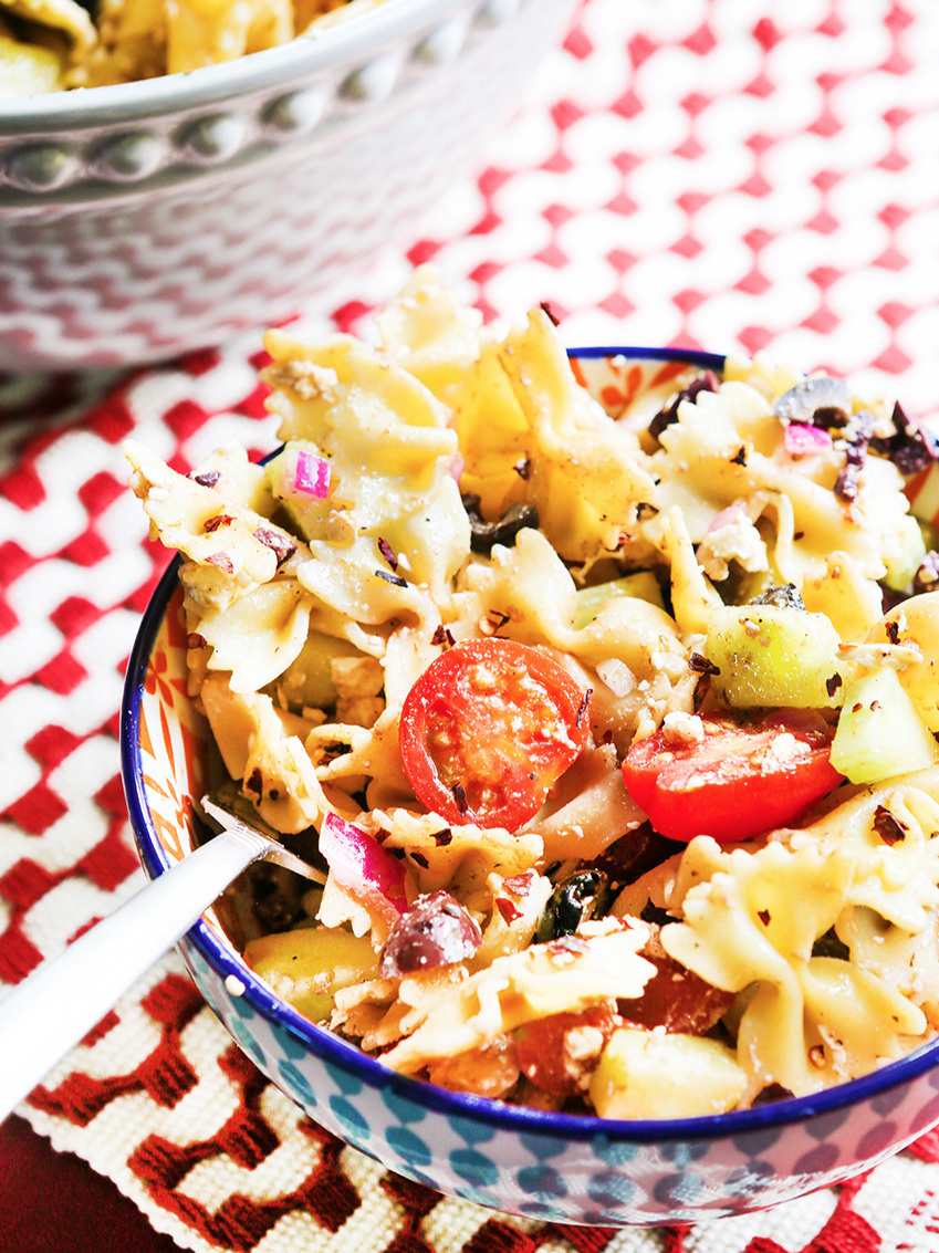close up of a bowl of mediterranean pasta salad with a fork in it