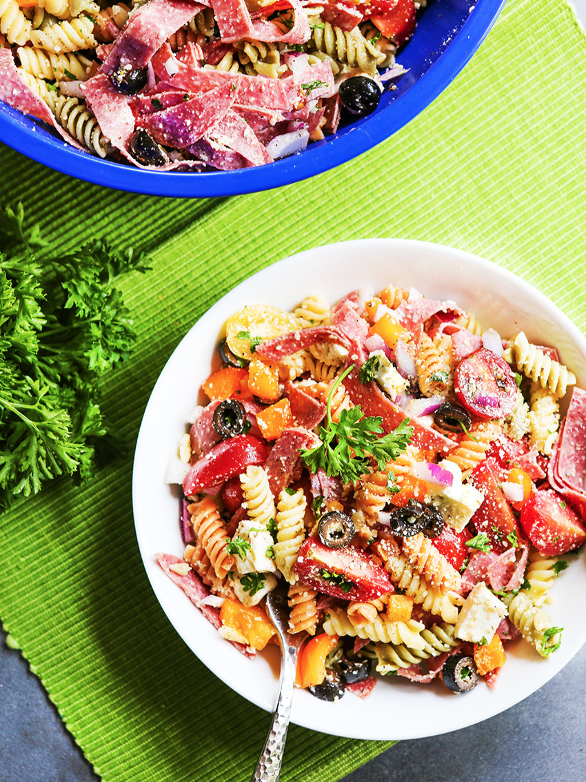 Looking down into small and large bowls of Italian pasta salad