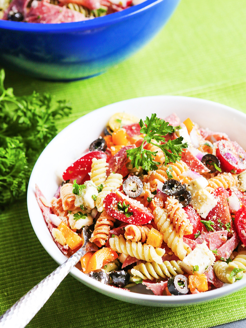 Serving of Italian pasta salad with mixing bowl in background