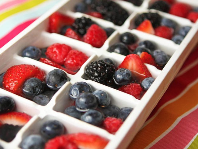 ice cube tray filled with fresh sliced fruit  and water over them