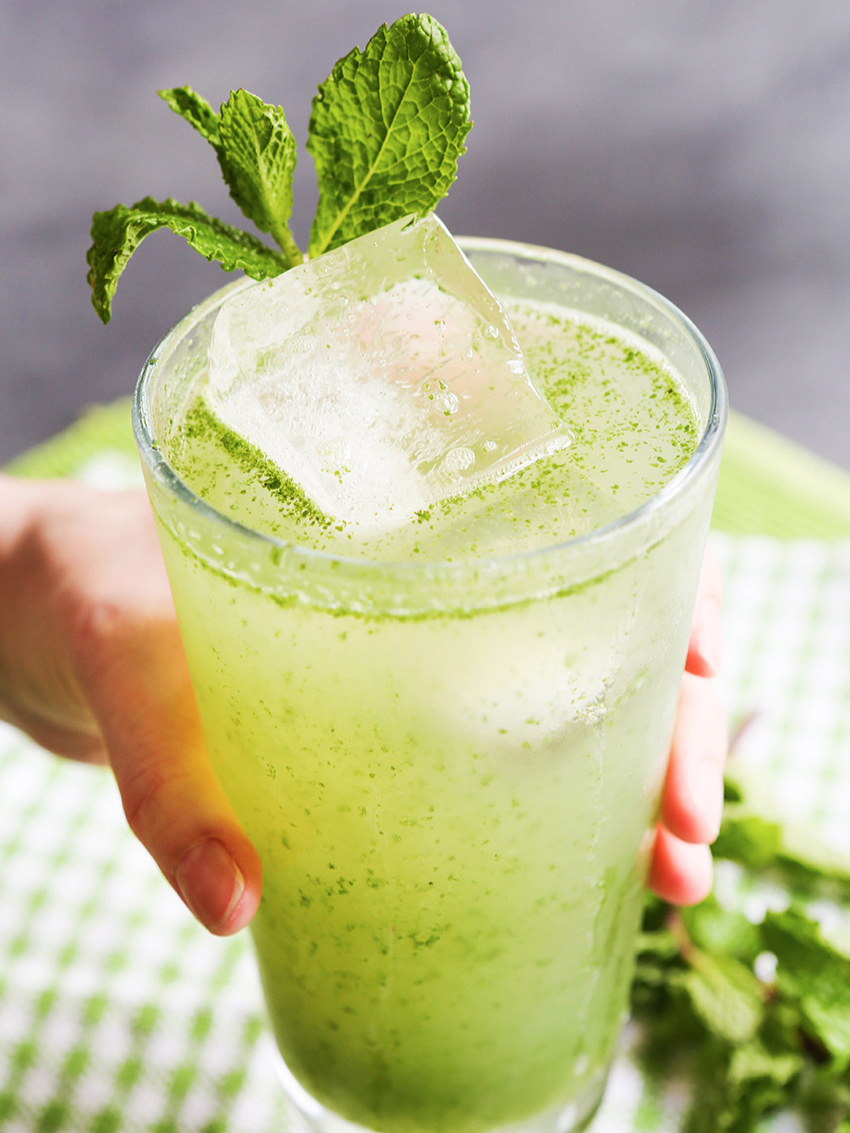 Hand holding out a green drink in a glass with a mint spring sticking out the top