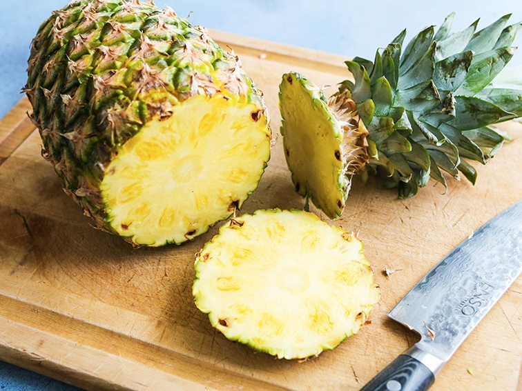 Pineapple with its top cut off sitting on a cutting board
