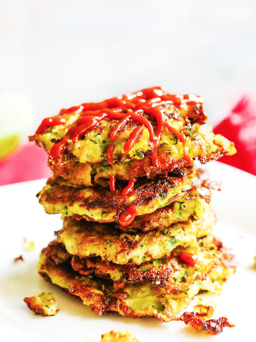 Close up of a stack of zucchini fritters on top of one another and sriracha drizzled over the stack.