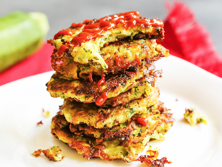 Stack of zucchini fritters on top of one another and sriracha drizzled over the stack.