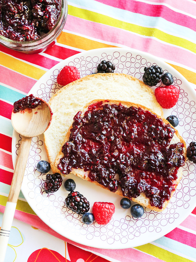 plate of bread with jam spread across and fresh berries around the toast, a wood spoon with a bit of jam lay on the plate and a jar of jam in the corner