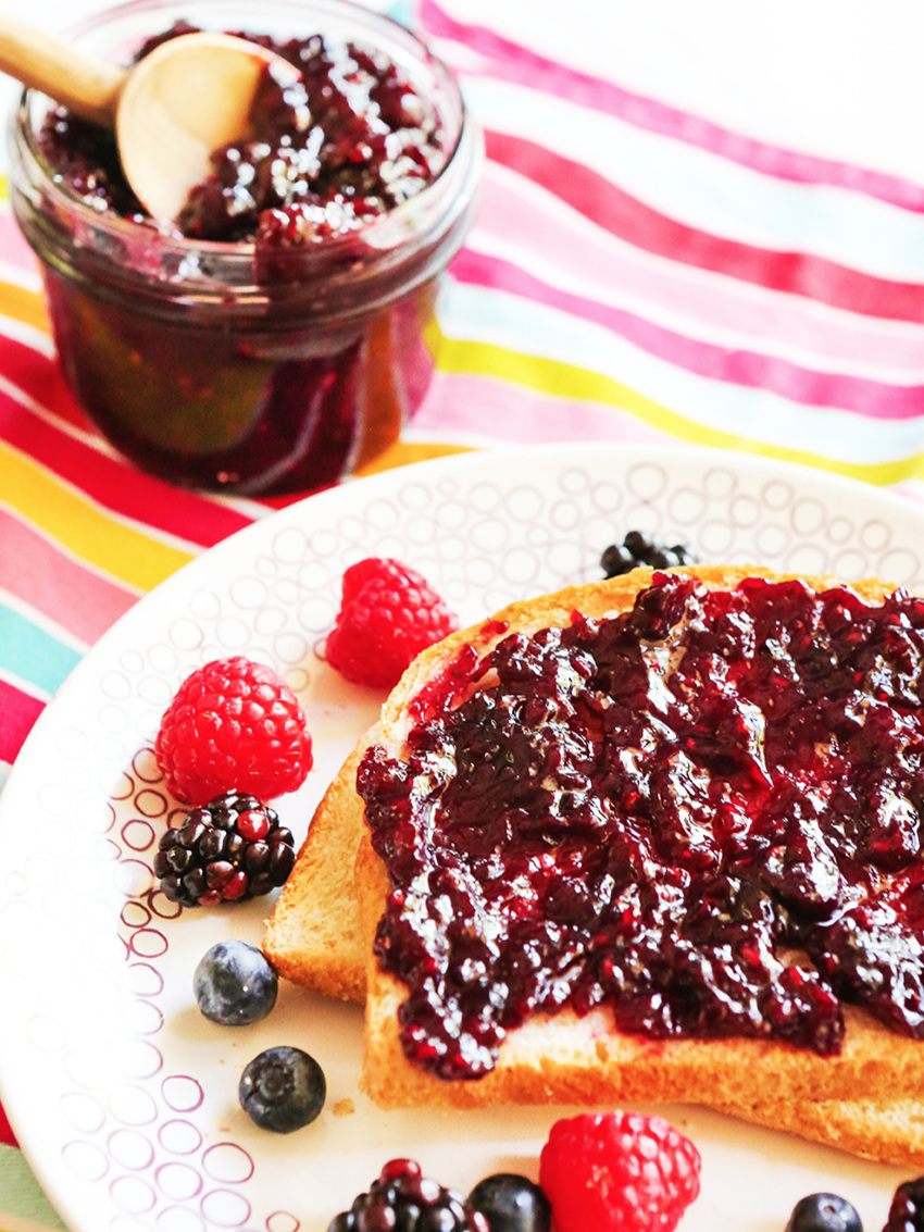 Slice of bread with cherry jam spread across on a plate with fresh berries around the plate and a jar of cherry jam next to it with a spoon inside