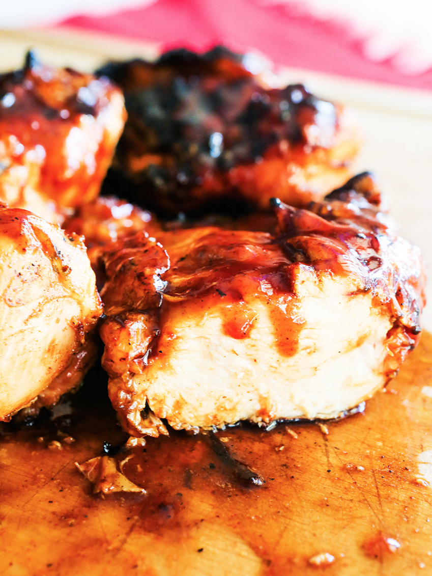 Pieces of grilled chicken cut in half and slathered in BBQ sauce.