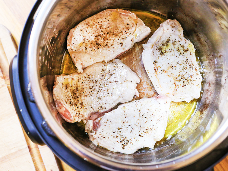 Four pork chops being sauteed in Instant Pot