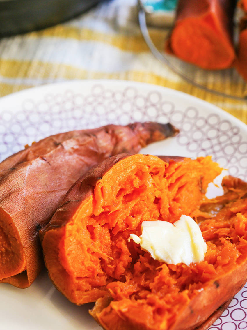 Instant Pot sweet potatoes cut in half with a pat of butter melting inside