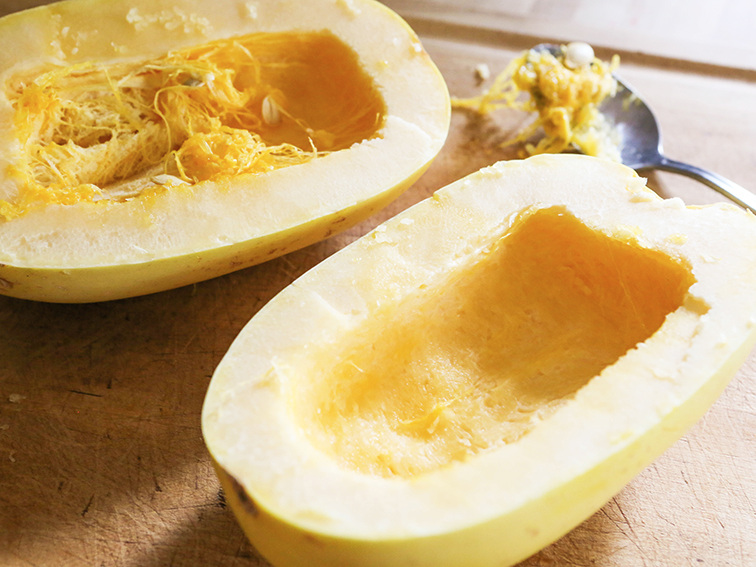 a spaghetti squash cut in half with one side of the seeds scooped out