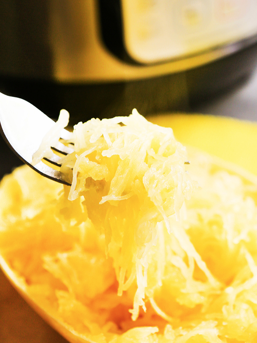 Fork tines filled with cooked spaghetti squash in front of an instant pot