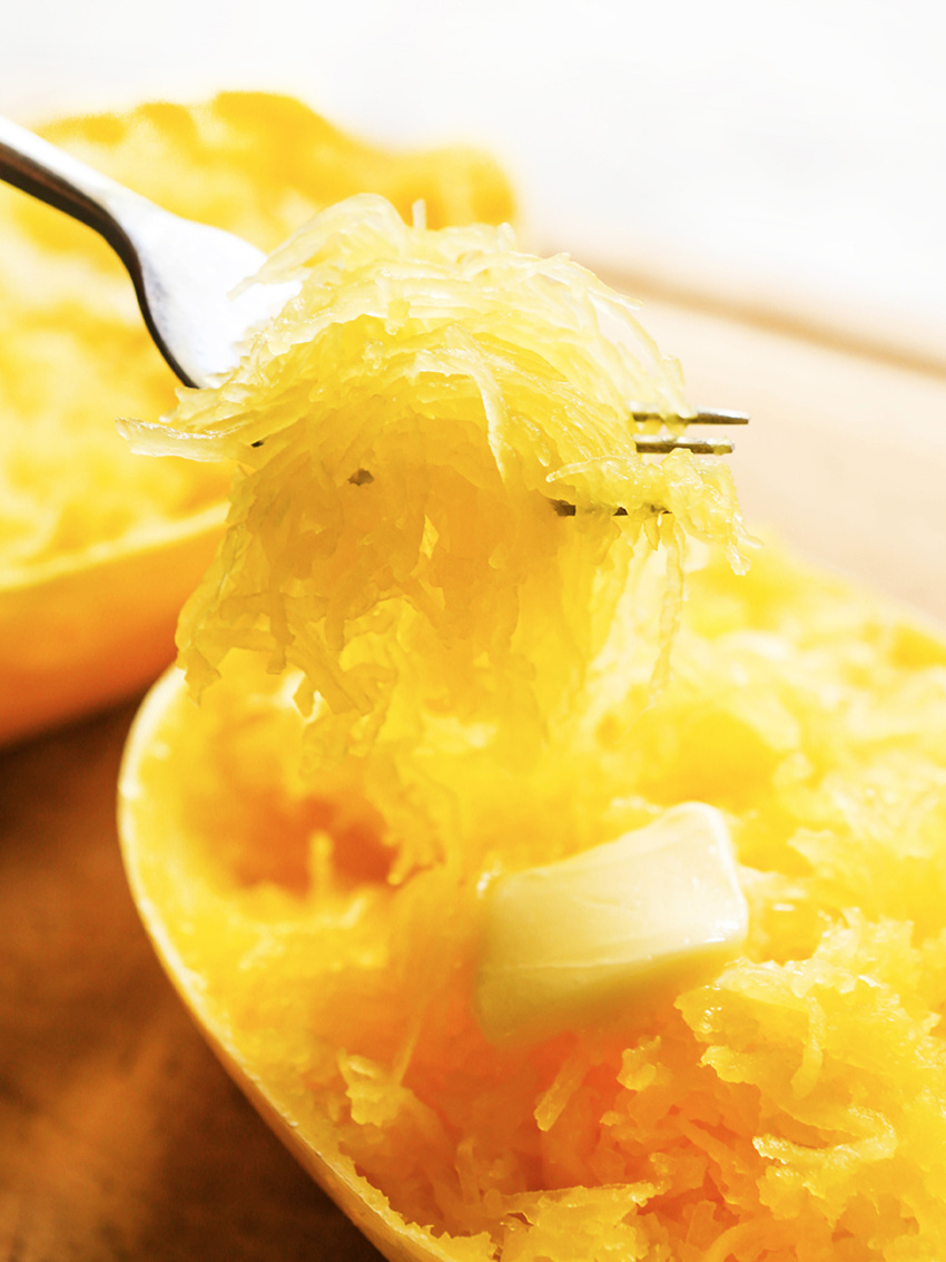 a pat of butter melting into instant pot spaghetti squash with a fork full of squash above it