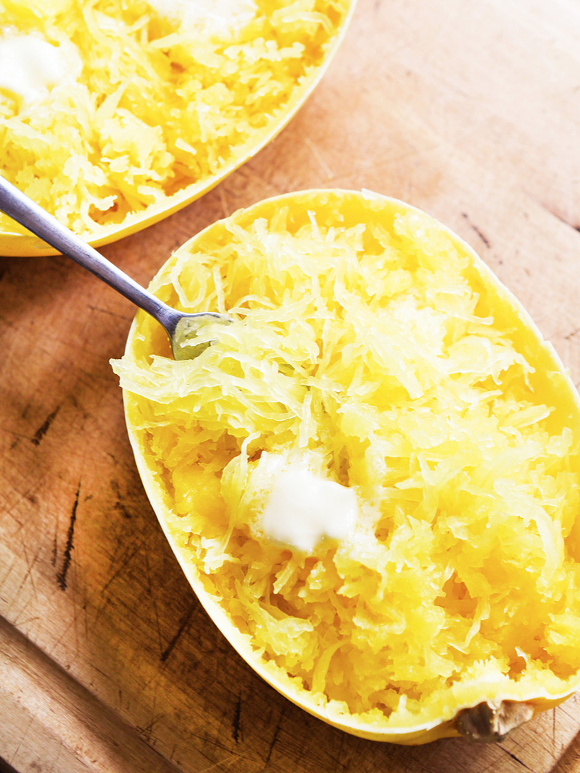 top view of a half spaghetti squash with a fork in it with melting butter on top