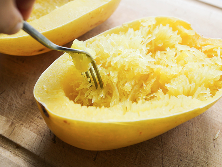 Instant Pot spaghetti squash cooked with a fork shredding the flesh