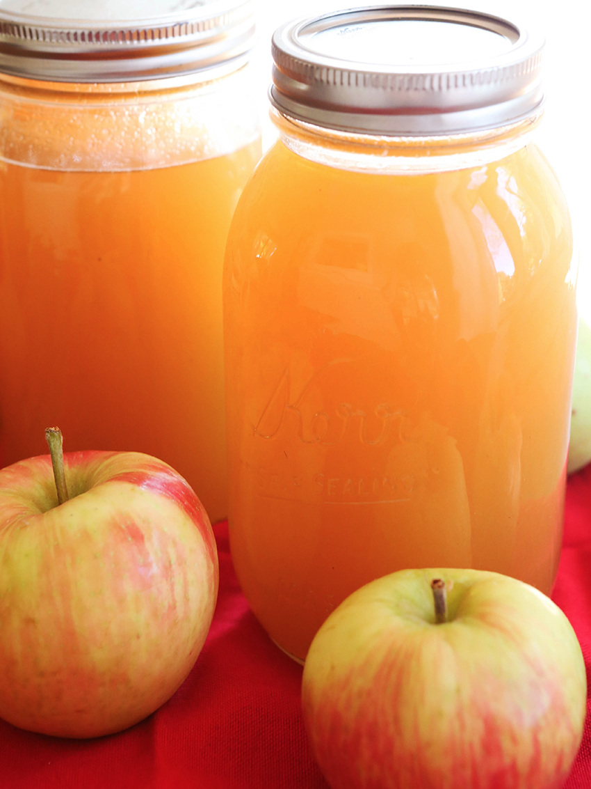 quarts of fresh homemade apple cider with whole apples in front of them