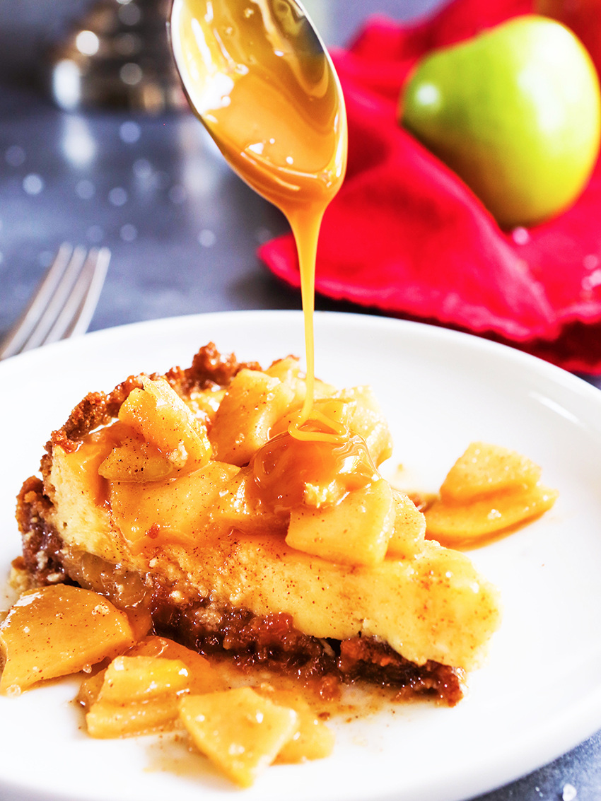 spoon drizzling caramel sauce over apple cheesecake