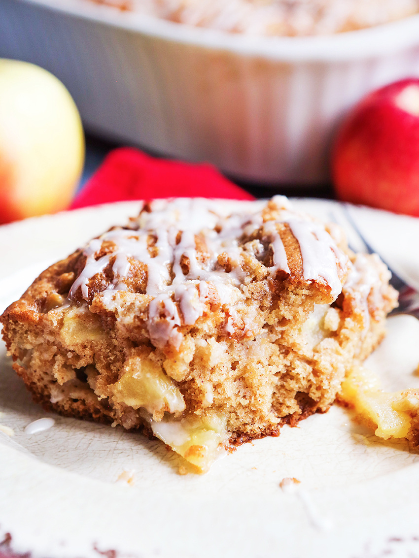 close up of piece of apple coffee cake on white plate