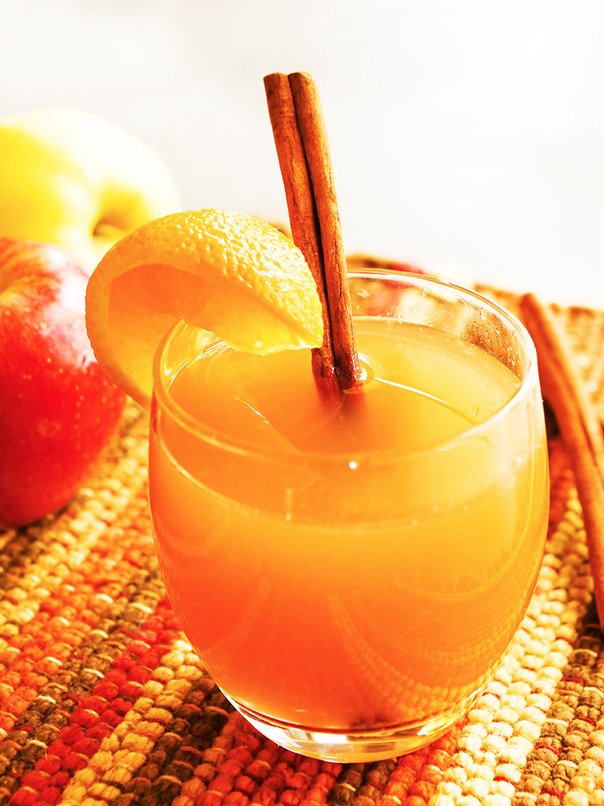 a glass of instant pot apple cider with an orange wedge and a cinnamon stick on the side