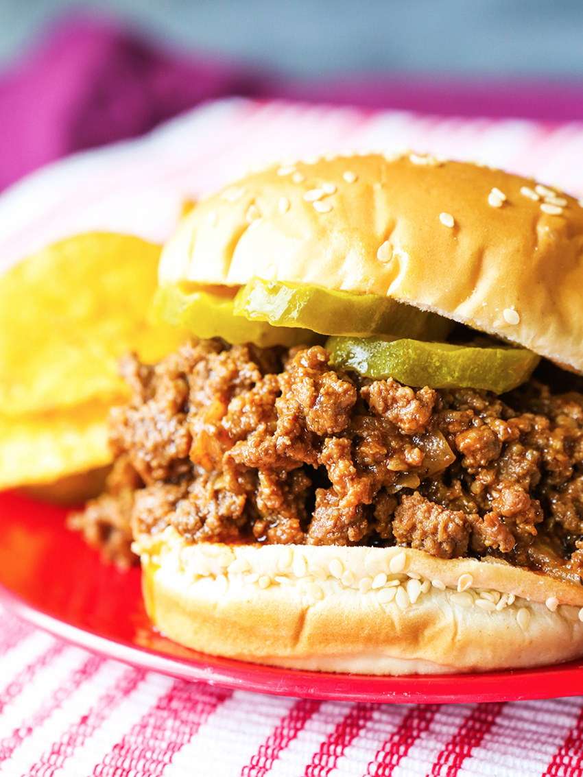 perfectly stacked sloppy joe on a red plate with chips