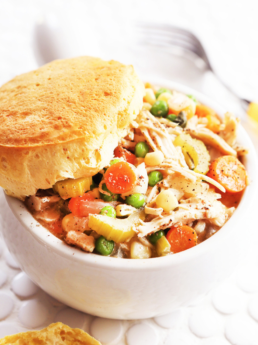 Chicken pot pie in a bowl with a biscuit on top