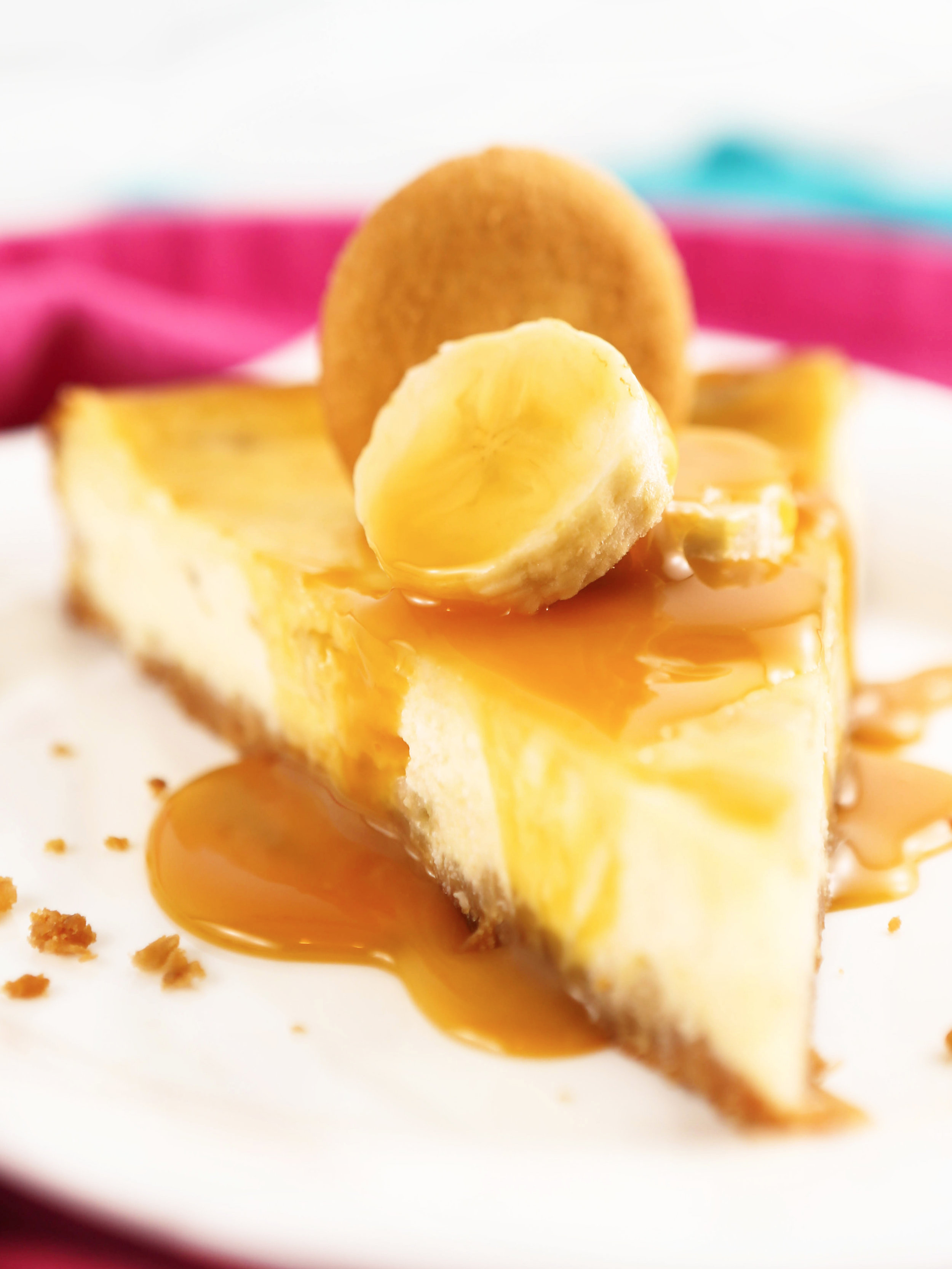 close up of a slice of banana cheesecake topped with caramel and a Nilla Wafer