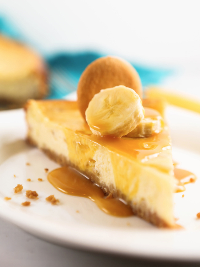 Slice of banana cheesecake with cookie and banana slices on top
