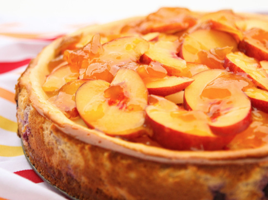 sliced peaches on top of baked cheesecake