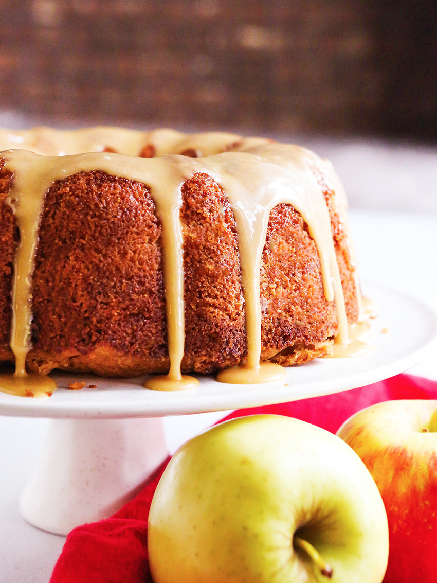 side view of an apple bundt cake with frosting on a cake display and apples on the table in front