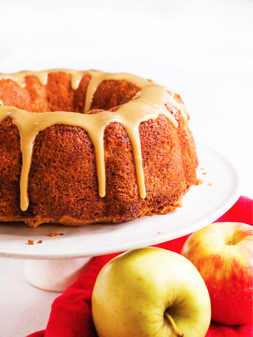apple bundt cake on a cake display tray with apples underneath it