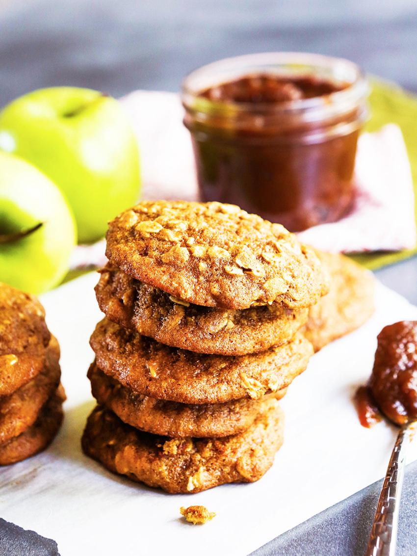 stack of apple butter oatmeal cookies with a spoonful of apple butter sauce on the side