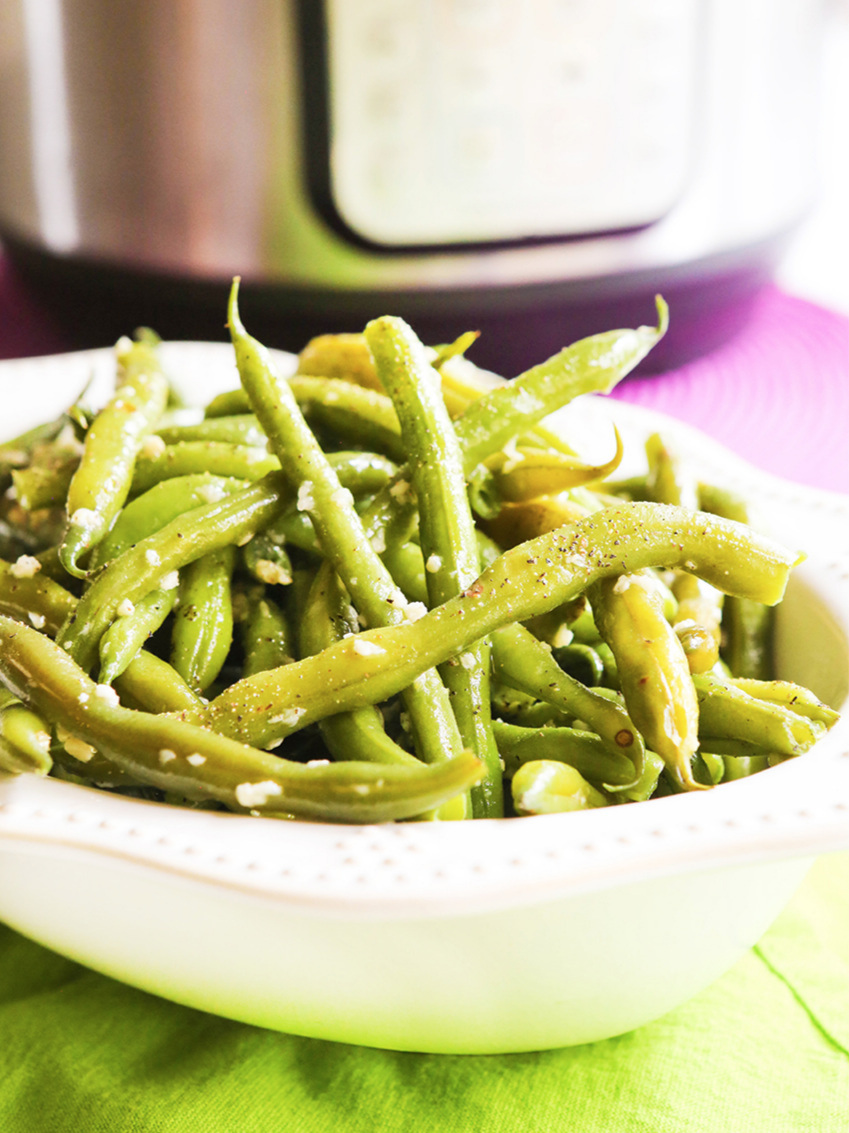 serving dish filled with cooked green beans and garlic sitting next to an instant pot