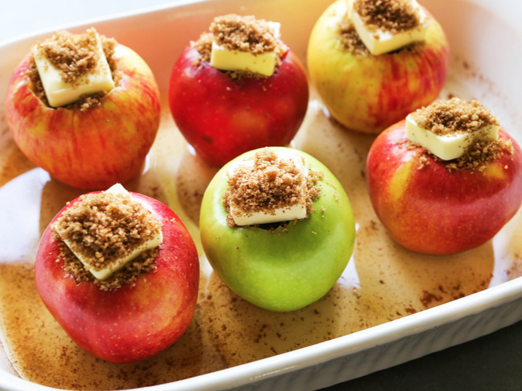 6 apples with pats of butter in a baking dish and brown sugar spooned over the tops of them