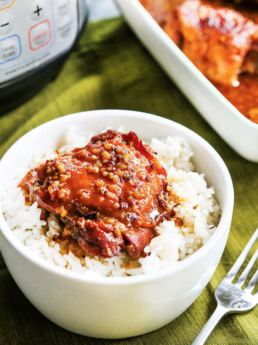 Bowl of instant pot honey garlic chicken and rice sitting next to the serving dish of chicken
