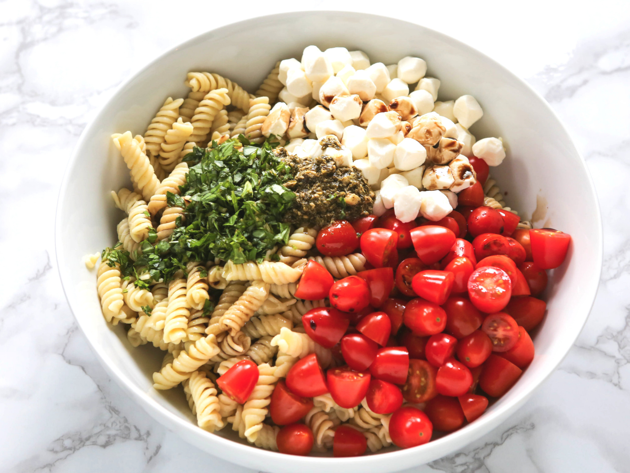 caprese pasta salad ingredients in mixing bowl