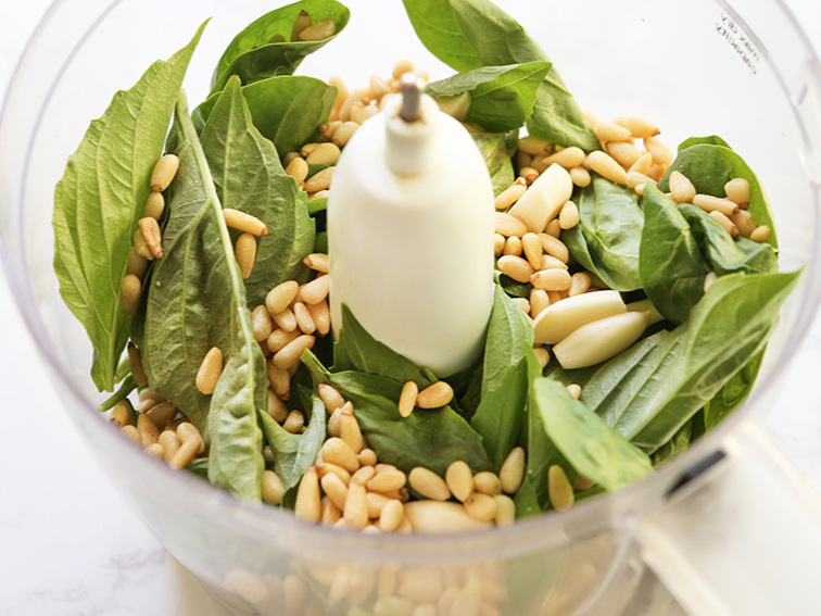 Food processor with basil leaves and pine nuts